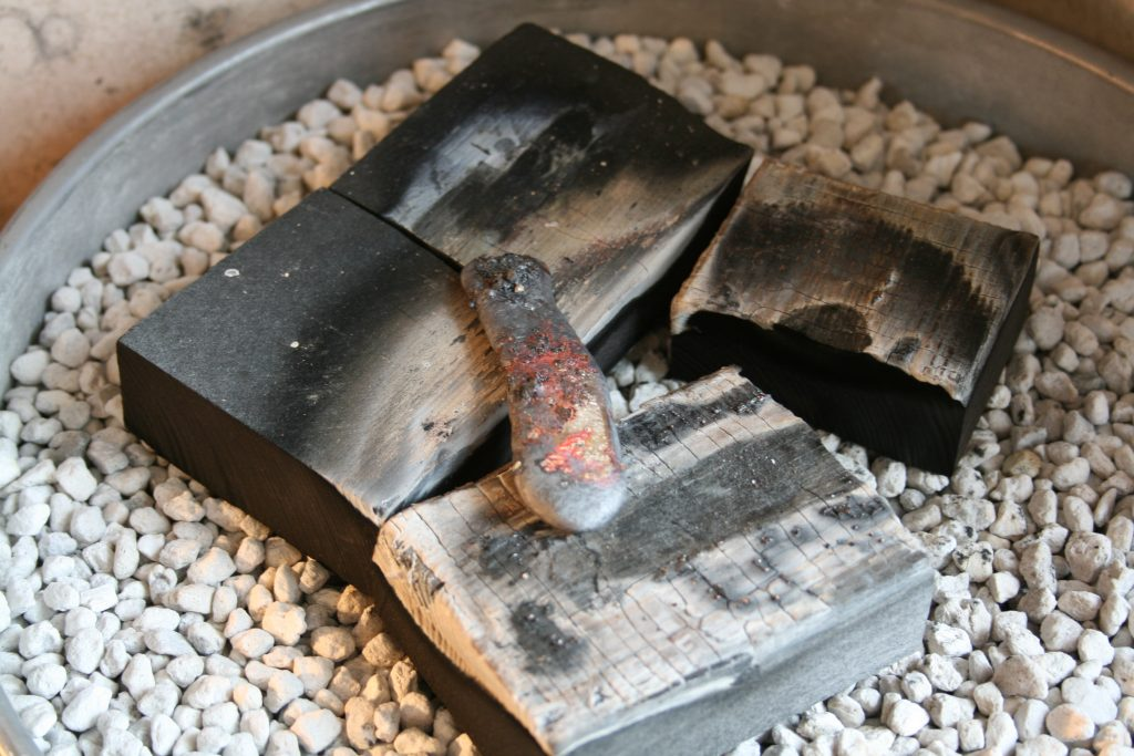 Recycled silver ingot on charcoal blocks
